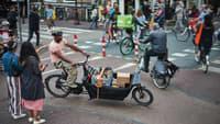 Handwerker fährt mit einem E-Lastenrad durch die Stadt