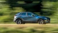 silberner Mazda CX 30 faehrt durch Landschaft