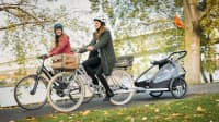 Zwei Frauen auf dem Fahrrad mit einem Fahrradanhänger fahren am Fluß
