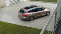 Beigener Ford Focus Turnier steht auf einem Parkplatz
