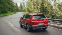 Roter Honda CR-V faehrt auf Strasse durch Wald