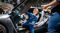 Kind steigt aus einem Sportwagen mit Fluegeltüren bei einer Automesse