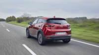 Der Mazda CX 3 Modelljahr 2021 fährt auf einer Strasse, von hinten aufgenommen.