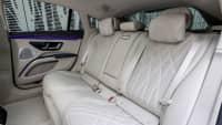 Die elegante Rückbank des neuen weißen Mercedes EQS 580 4MATIC mit den weißen Gurten und Ledersitzen