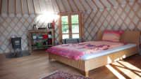 Eine Jurte von Innen mit Bett, Fenster und Regal