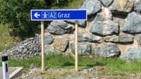 Ein neues Holz-Verkehrsschild in Österreich mit Pfeil zur Autobahn A2 Richtung Graz