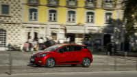 ein roter Nissan Micra fährt durch die Stadt