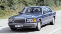 Dunkelblauer Mercedes-Benz der Baureihe 126 fährt auf einer Landstraße