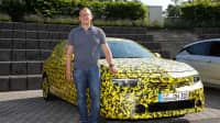 Jochen Wieler steht bei der Testfahrt an dem noch getarnten Opel Astra