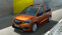 Ein orangefarbener Opel Combo e life, ein elektrischer Combo, während der Fahrt auf einer modernen betonwandgesäumten Strasse