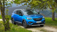 Blauer Opel Grandland X faehrt durch Gelaende
