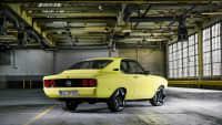 Ein gelber Opel Mantra mit Elektroantrieb steht in einer alten Fabrikhalle