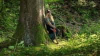 Ein Mann Mit einer Axt lehnt gegen einen Baum im Wald