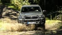 Toyota Hilux fährt über einen matschigen Waldweg