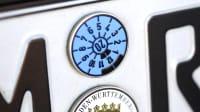 eine blaue TÜV-Plakette auf einem Nummernschild
