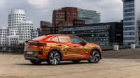 VW ID5 steht vor futuristischen Häusern