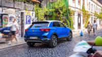 blauer VW T-Roc steht in einer Stadt