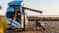 Der Grand Canyon S mit Aufstelldach am Strand beladen mit Surfbrettern