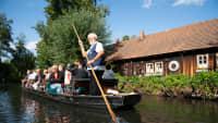 Ein Mann steuert einen Kahn auf einem Fluss mit einer langen Holzstange