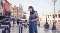 Eine Frau schaut in Verona auf einem Platz, vor einem Restaurant, in eine Speisekarte.