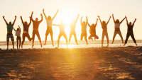 Junge Leute springen am Strand bei untergehender Sonne in die Luft.