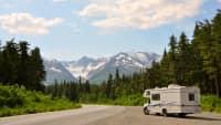 Wohnmobil steht vor Berglandschaft in Alaska