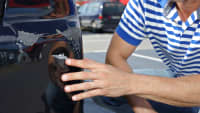 Mann zeigt auf Schaden an seinem Auto