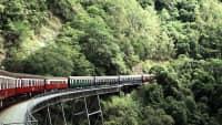 Ein Zug der Kuranda Scenic Railway fährt in Australien über eine Brück in den Dschungel