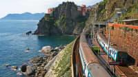 Ein Zug fährt in Cinque Terre in Italien direkt am Meer
