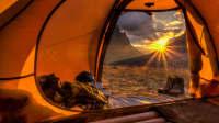 Blick durch ein orangenes Zelt in den Sonnenuntergang
