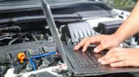 Männerhände an Laptop auf dem Motor eines Autos
