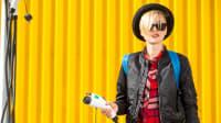 Junge Frau steht vor gelbem Container mit dem Ladekabel für ein Elektroauto in der Hand
