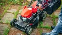 Mann füllt Rasenmäher mit Benzin
