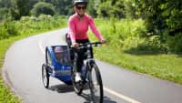 Mutter fährt Fahrrad mit Kind im Fahrradanhänger