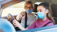 Mädchen und Fahrlehrerin mit Mundschutz im Auto