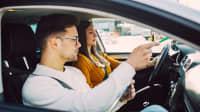 Ein Fahrlehrer erklärt seiner Schülerin die Regeln auf dem Beifahrersitz