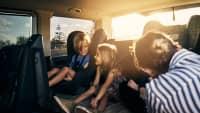 Mutter lacht mit drei Kindern auf der Rückbank eines Autos