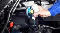 Automechaniker prüft den Stand des Frostschutzmittels