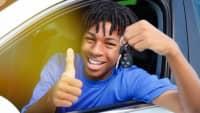 Junger Mann sitzt in Auto mit Autoschlüssel in der Hand
