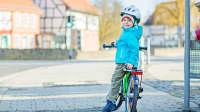 Kind mit Rad auf dem Gehweg