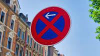 Schild mit absolutem Halteverbot in der Stadt vor blauem Himmel