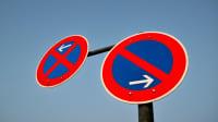Schilder für absolutes und eingeschränktes Halteverbot vor blauem Himmel