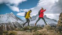Junges Paar hüpft über die Steine dahinter Berggipfel