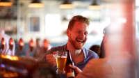 Ein junger Mann trinkt Bier in einer Bar