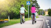 zwei Kinder fahren auf dem Gehweg mit dem Rad