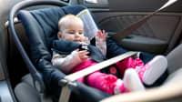 Baby sitzt im Kindersitz im Auto und ist angeschnallt