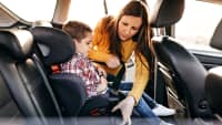 Mutter fixiert Kindersitz im Auto