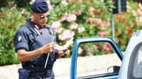 Italienischer Polizist kontrolliert Papiere eines Autofahrers