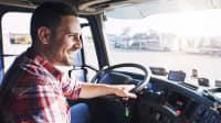 Ein Mann fährt lächelnd einen LKW