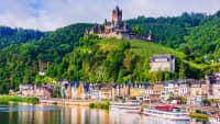 Eine Stadt an einem Fluss, mit Schiffen und über der Stadt liegt eine Burg auf einem Berg